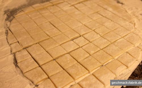 ausgerollter Teig in kleine Quadrate geschnitten